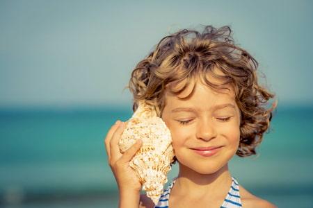 Une fille écoute un coquillage et imagine des histoires