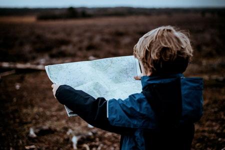Un garçon regarde une carte et cherche un bon trajet